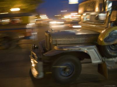 Jeepney Speeds Through Night in Malate-Greg Elms-Photographic Print