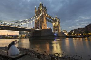 A Bride and Groom Kiss in Front of Tower Bridge at Sunset by Jeff Mauritzen