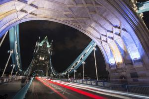 Cars Drive Past in a Blur of Motion at Night Atop the Tower Bridge in London, England by Jeff Mauritzen