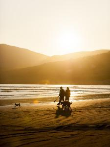 The Sun Sets Behind a Couple Walking on the Beach with their Two Dogs at Inch Beach by Jeff Mauritzen