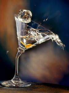 Vodka Martini Spilling from a Bent Martini Glass with Ice Cube by Jeff Sarpa