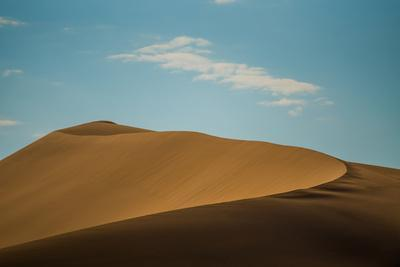 A large sand dune curves under a cloud in the desert.