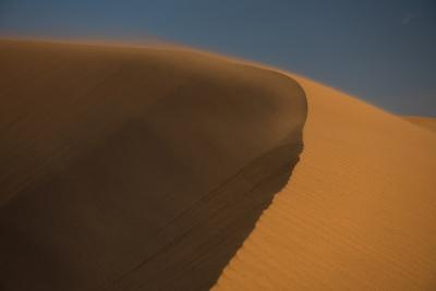 Wind blows sand over a large dune in the desert.