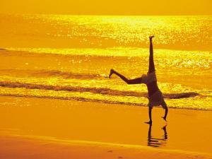 Girl Doing Cartwheels on Beach at Sunset by Jennifer Broadus