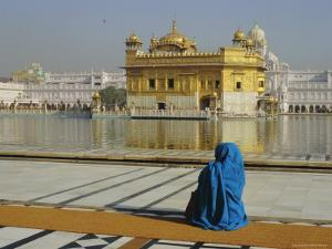 A Pilgrim in Blue Sits by the Holy Pool of Nectar at the Golden Temple, Punjab, India by Jeremy Bright