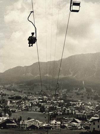 Man Riding Chair Lift Above Town