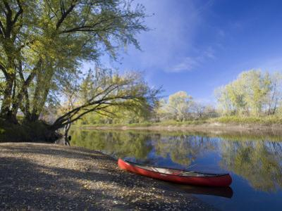 A Canoe rests on the banks of he Connecticut River in Maidstone, Vermont, USA