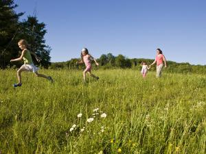 Hikeers walk in a field in Sabins Pasture, Montpelier, Vermont, USA by Jerry & Marcy Monkman