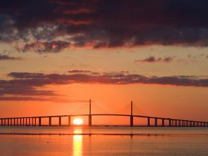 Sun Rises Behind the Sunshine Skyway Bridge, Pinellas County, Florida by Jerry & Marcy Monkman