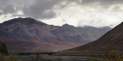 Tourist bus driving among mountains in the Denali National Park, Alaska, United States of America,