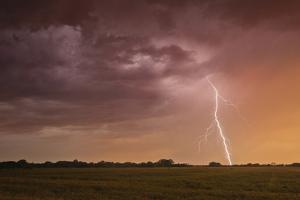 A Cloud-To-Ground Bolt of Lightning Strikes Beneath a Thunderstorm at Sunset by Jim Reed
