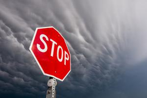 A Dark Storm Looms over a Bright Red Stop Sign by Jim Reed