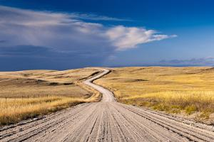 A Deserted Gravel Road Winding Through Rural Land by Jim Reed