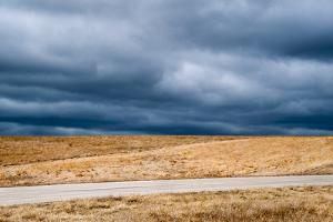 A Deserted Highway Cuts Through a Picturesque Landscape Beneath a Stormy Sky by Jim Reed