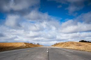 A Deserted Highway Leads Up a Hill Toward a Beautiful Sky Full of Clouds by Jim Reed