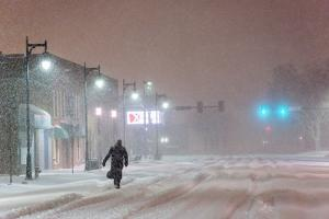 A Man Trudges Through Deep Snow on His Way to Work During a Predawn Snowstorm by Jim Reed