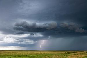 A Positive Cloud-To-Ground Bolt of Lightning Strikes Beneath a Thunderstorm by Jim Reed
