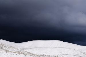 A Powerful Winter Storm Approaches Snow-Covered Mountains by Jim Reed
