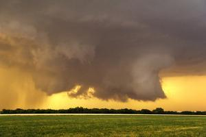 A Supercell Thunderstorm Produces a Wall Cloud and Developing Tornado over a Farm Field at Sunset by Jim Reed