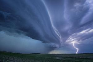 A Supercell Thunderstorm Produces Cloud-To-Ground Lightning During Twilight by Jim Reed