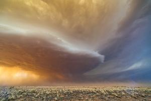 A Supercell Thunderstorm Rotates over a Field at Sunset by Jim Reed