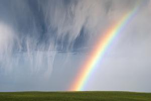 A Thunderstorm Produces a Curtain of Falling Hailstones Next to a Rainbow by Jim Reed