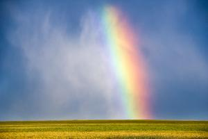 A Thunderstorm Produces a Vibrant Rainbow by Jim Reed