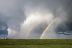 A Thunderstorm Produces a Vivid Double Rainbow Next to a Curtain of Falling Hailstones by Jim Reed