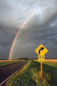 A Thunderstorm Produces a Vivid Rainbow over a Rain-Soaked Paved Road by Jim Reed