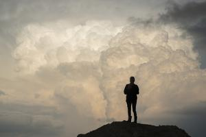 A Woman in Silhouette Watches a Picturesque Storm from Atop a Hill by Jim Reed