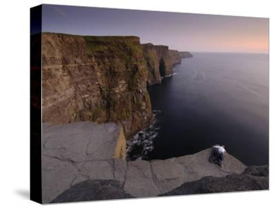 A Couple Lies on Rocks Overlooking the Cliffs of Moher and the Sea
