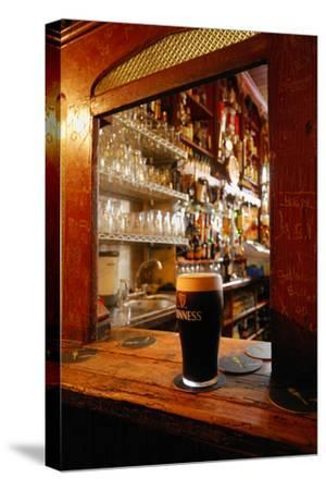 A Pint of Dark Beer Sits in a Pub Service Window by Jim Richardson
