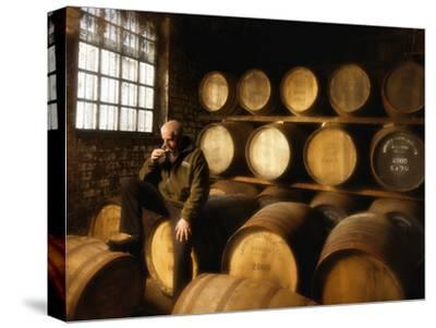 A Worker Tastes Whisky in a Distillery Surrounded by Aging Barrels