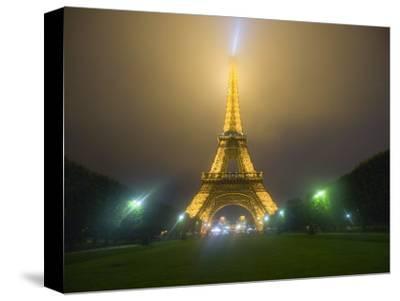 Eiffel Tower Illuminated in Fog and Rain at Night, Paris, France