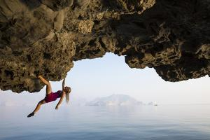 A climber dangles from an overhang. by Jimmy Chin