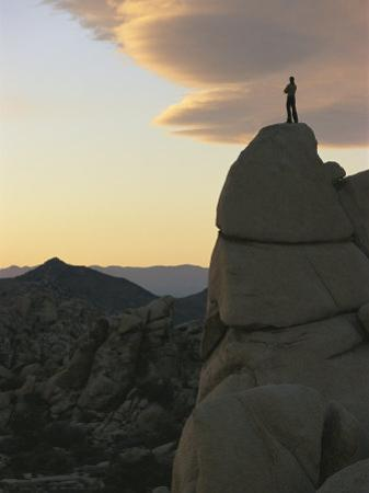 A Climber Watches the Sunset from High Atop a Rock Formation