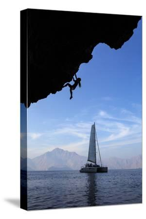 A Climber, Without Ropes, Scales an Overhang