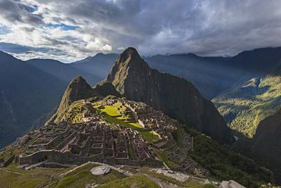 Light Streams Through The Clouds And Lights Parts Of The Ancient City Of Machu Picchu