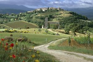 Abbey of Sant' Antimo, Tuscany. Hill Town of Castelnuovo Dell' Abate in Background by Joe Cornish