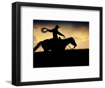 A Silhouetted Cowboy Riding Alone a Ridge at Sunset in Shell, Wyoming, USA