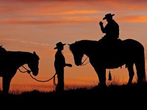 Cowboy and Cowgirl Silhouetted on a Ridge in the Big Horn Mountains, Wyoming, USA by Joe Restuccia III