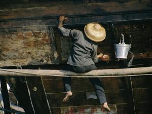 A Chinese Woman Scrubs the Outside of a Junk by Joe Scherschel