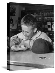 Boy Wearing Baseball Uniform Eating Banana Split at Soda Fountain Counter by Joe Scherschel