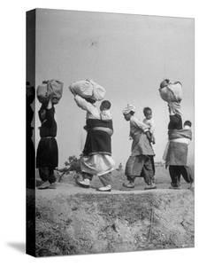 Carrying Belongings, South Korean Mothers and Children Flee North Korean and Red Chinese Forces by Joe Scherschel
