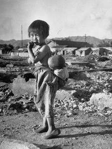 Girl Standing in Rubble from the Korean Civil War, Carrying a Baby in a Sling on Her Back by Joe Scherschel