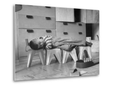 Rocky Stensrud, Jr., Using Children's Chairs in a Home to Make a Train Upon Which He Can Sleep