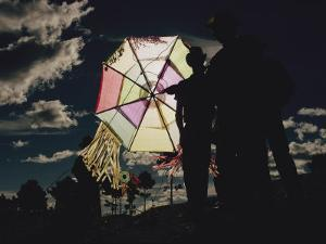Several Men Hold a Kite That is Backlit by the Sun by Joe Scherschel