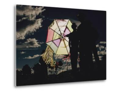 Several Men Hold a Kite That is Backlit by the Sun
