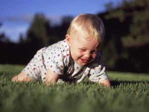 A Baby Boy Crawls Through the Green Grass by Joel Sartore