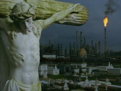 A Crucifixion Statue in Holy Rosary Cemetery Overlooks Petrochemical Plants by Joel Sartore